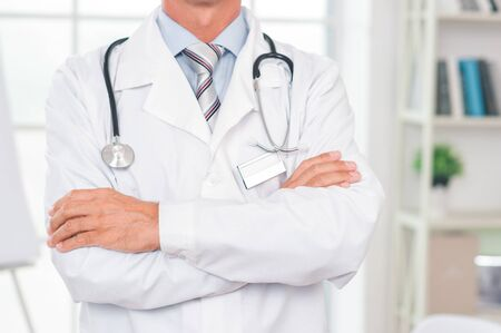Senior man doctor at his office in clinic close-up standing confident crossed arms Stockfoto