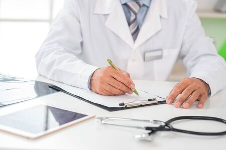 Senior man doctor at his office in clinic close-up sitting writing prescription Stockfoto