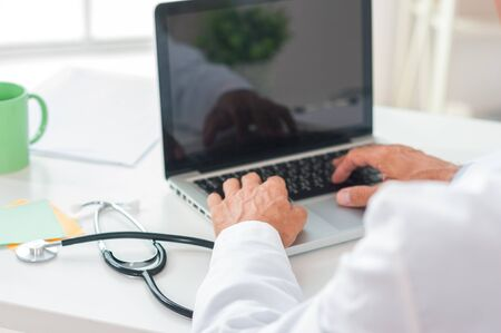 Senior man doctor at his office in clinic close-up sitting using laptop typing back view copyspace