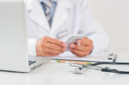 Senior man doctor at his office in clinic close-up sitting using laptop holding smartphone communication