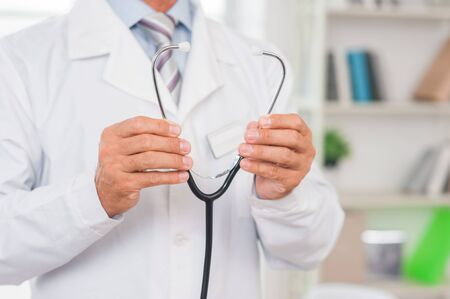 Senior man doctor at his office in clinic close-up standing holding stethoscope