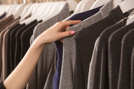 Cropped view of young adult woman choosing new clothes in shopping center, holding hand on soft gray knitted wear