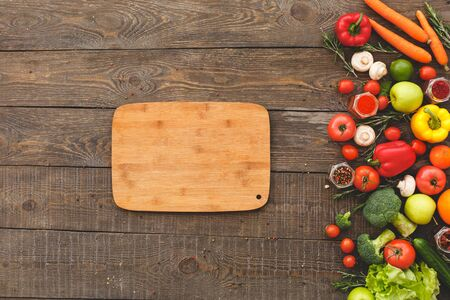 On the right are the vegetables and on the left a cutting board. Wooden background top view mock-up