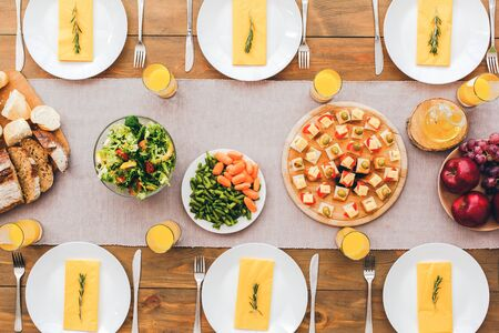 Flat lay view of holiday table setting with tablecloth, plated, juice in glass and delicious appetizer food on wooden surface Stockfoto