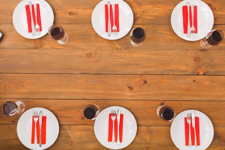 Plates, six glasses with red wine. Festive table set for six people. Wooden background top view mock-up. Wooden background top view mock-up