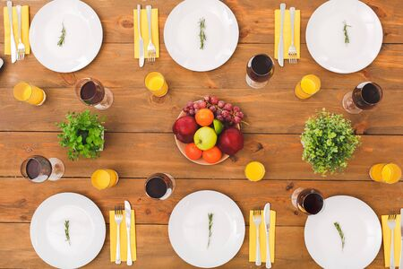 Flat lay view of table setting for family dinner at birthday celebration with ceramic plate, juice and wine in glass on wooden surface