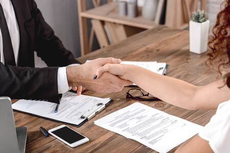 Male employer having job interview with female candidate shaking hands accepted sitting in office close-up