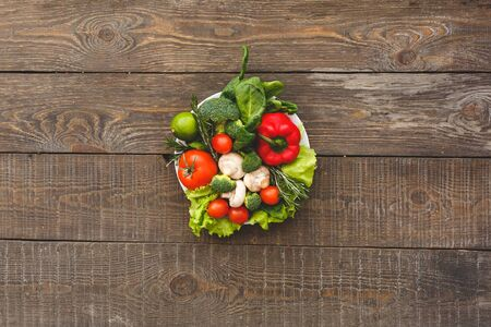 Colorful picture of plate of salad. Wooden background top view mock-up