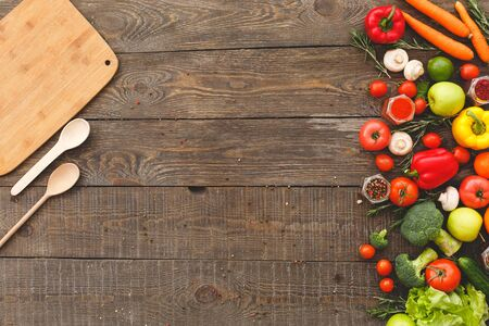 Left board and spoons on the right vegetables, in the middle copy space. Wooden background top view mock-up