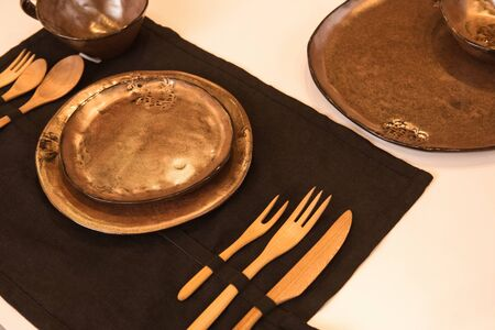 Fancy and beautiful table setting with set of ceramics kitchenware on black textile tablecloth with wooden cutlery