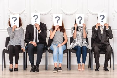 Group of people candidates men and women sitting on chairs waiting for job interview holding paper with quaestion mark choice