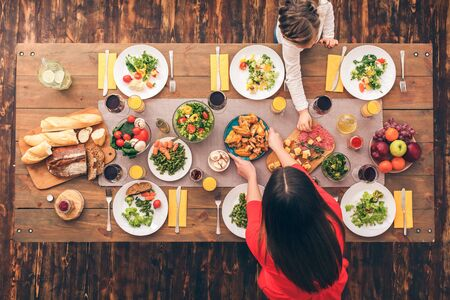 Young woman and her daughter putting food on table. Festive table set for six people. Wooden background top view mock-up Stockfoto