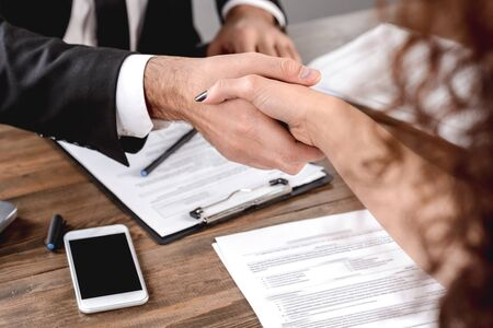 Male employer having job interview with female candidate shaking hands signing contract sitting in office close-up Stockfoto