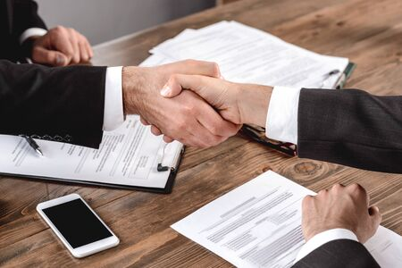 Employer and candidate sitting in office having job interview shaking hands deal close-up Stockfoto