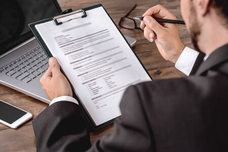Employer assessing candidate filling form sitting in office back view close-up