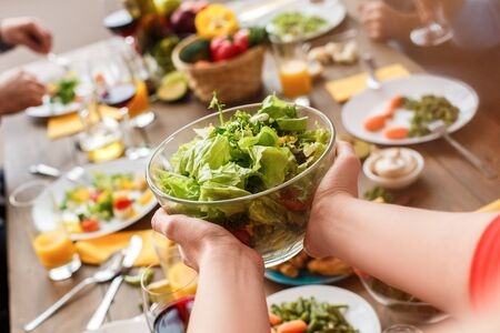 Focus on a useful salad in the hands of the woman. Vegetarian food concept Stockfoto