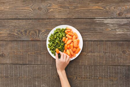 Woman take some carrots and beans lie on a plate. Wooden background top view mock-up Stockfoto