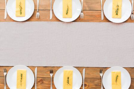 White plates and yellow napkins. Festive table set for six people. Wooden background top view mock-up