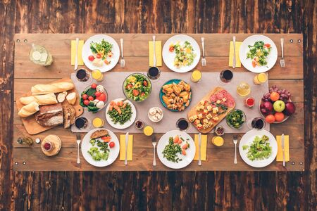 Flat lay view of family festive and beautiful holiday table setting with silver cutlery, tablecloth, ceramic plates and delicious food on wooden surface