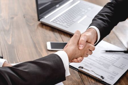 Employer and candidate sitting in office having job interview shaking hands agreement close-up