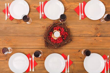 Flat lay view of beautiful and fancy table setting with empty ceramic plate, candle and wine in glass for family dinner at christmas eve on wooden table