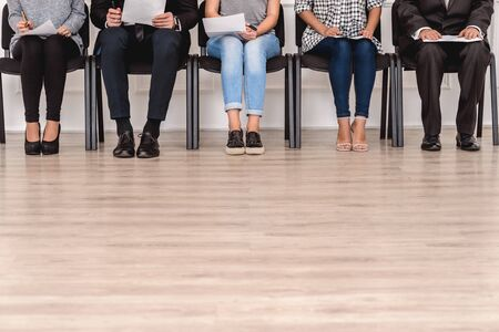 Group of people candidates men and women sitting on chairs waiting for job interview holding resume floor and legs close-up