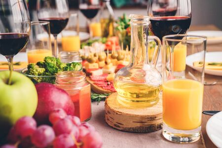Assorted food, with drinks set on wooden table with tablecloth at family banquet. Glasses of wine and fresh juice near delicious meal