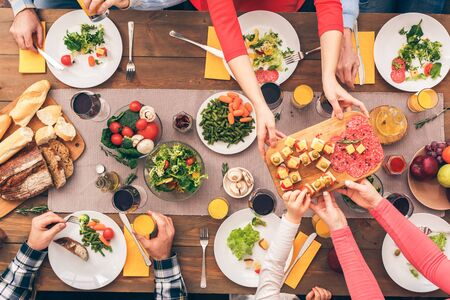 Mom handing food to her daughter. Festive table set for six people. Wooden background top view mock-up