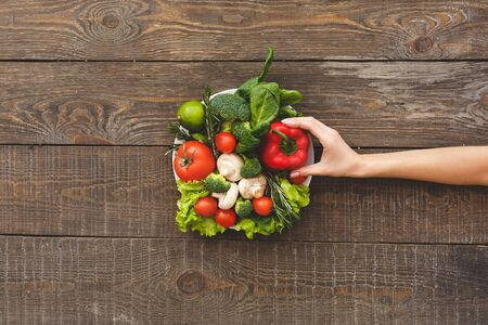 Woman touching red pepper on salad. Wooden background top view mock-up Stockfoto
