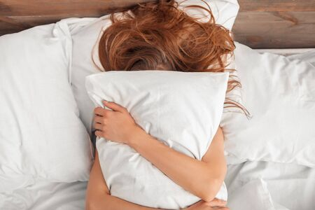 Young woman lying on bed morning at home hugging pillow covering face top view