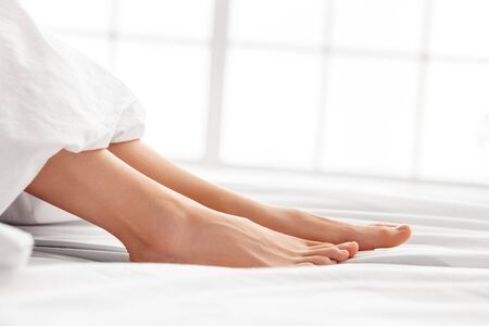 Young woman lying on bed morning at home feet under blanket side view close-up