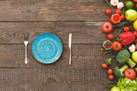 Fork, knife, near lie many vegetables. Wooden background top view mock-up Stockfoto