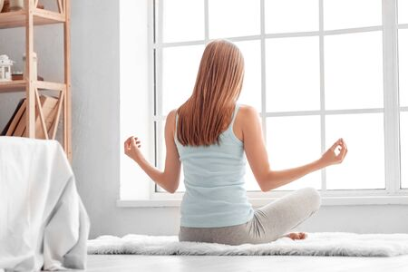 Young woman exercise at home on carpet sitting meditating peaceful back view