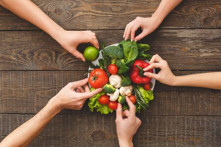 Flat lay view of family holding raw vegetables and ripe organic ingredients in hands, over plate with healthy food on wooden table