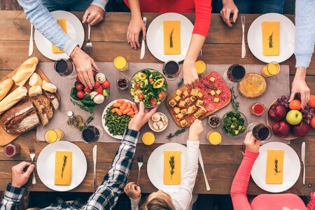Big family starts lunch or dinner. Festive table set for six people. Wooden background top view mock-up