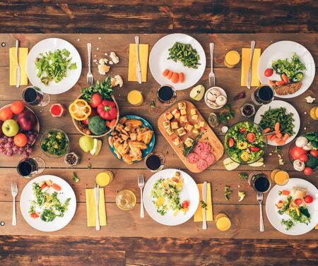 Colorful festive table with a huge amount of delicious, healthy food. Festive table set for six people. Wooden background top view mock-up. Wooden background top view mock-up