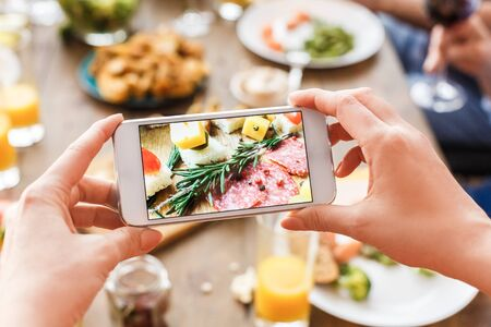 Cropped view of adult woman making photo with food on her modern smartphone, while she celebrate traditional hanukkah dinner together with family