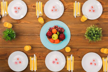 Flat lay view of table setting with food and drinks, fruits and plant decoration for family dinner on wooden surface