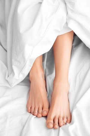 Young woman lying on bed morning at home legs under blanket top view close-up Standard-Bild