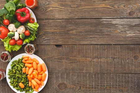 Vegetables, carrots and beans lie on a plate. Wooden background top view mock-up Standard-Bild