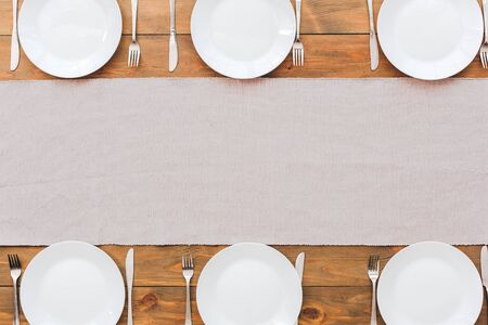 Minimalism. White plate's and gray tablecloth. Festive table set for six people. Wooden background top view mock-up