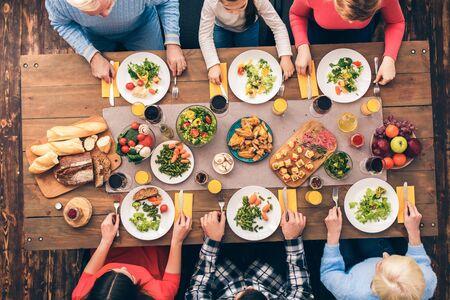 Ogni membro della grande famiglia mangia. Tavola delle feste apparecchiata per sei persone. Mock-up vista dall'alto su fondo in legno