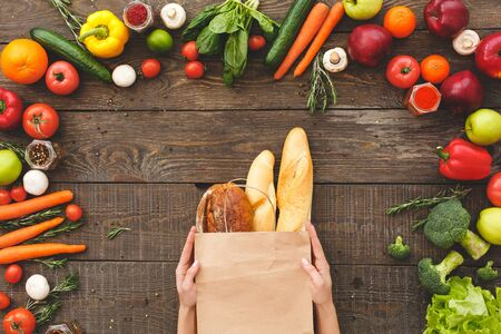 Flat lay view of woman hands with paper bag, fresh bread and baguette on wooden table near raw organic vegetables with raw ingredients for healthy cooking at home