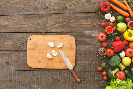 On a cutting board chopped mushroom and knife, next to lie vegetables. Wooden background top view mock-up