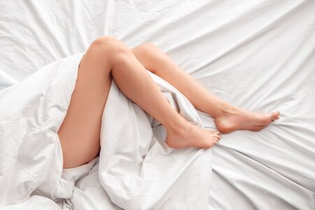 Young woman lying on bed morning at home legs top view close-up