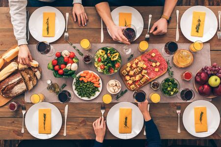 Cropped view of people sitting at home behind table with delicious food, celebrate traditional hanukkah dinner together, top view Standard-Bild