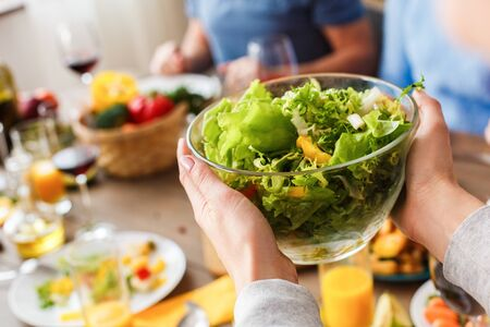 Cropped view of adult woman holding glass bowl with green fresh salad over table, spending time together with family on traditional dinner at weekend Standard-Bild