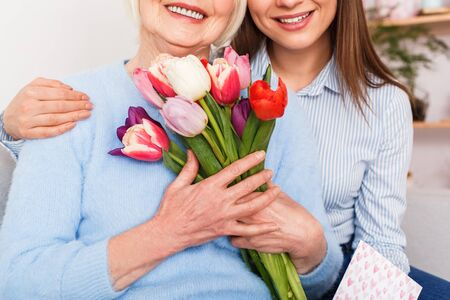 Old woman toothy smiled with a daughter embrace and holding flowers Standard-Bild
