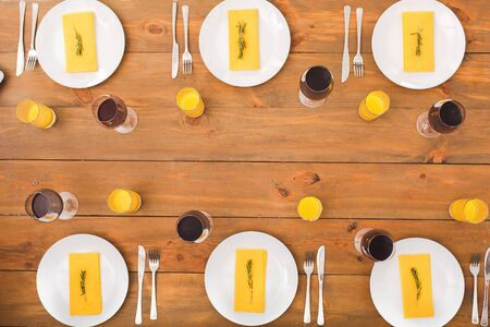 Yellow and red decor at home table. Festive table set for six people. Wooden background top view mock-up. Wooden background top view mock-up