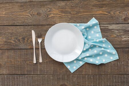 Minimalism. Blue towel, white plate, knife and fork. Wooden background top view mock-up
